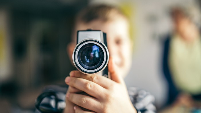Male student holding a camera and looking into it.